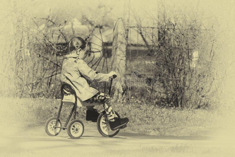 Meisje op een three-wheeled retro fiets stock foto's