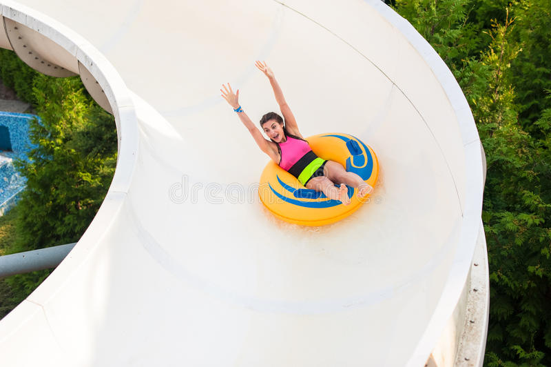 Meisje op een waterdia, gelukkig glimlachen stock foto