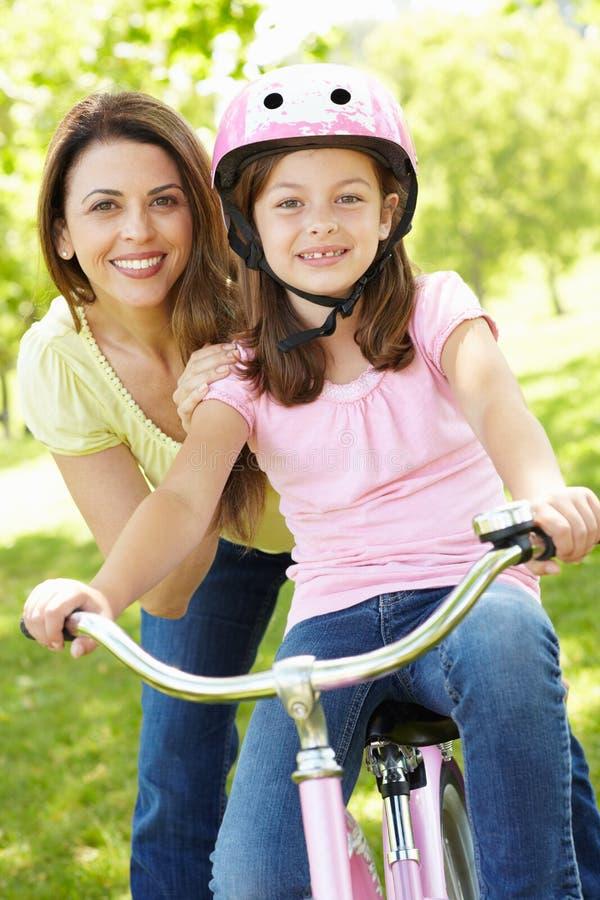 Meisje op fiets met moeder royalty-vrije stock fotografie