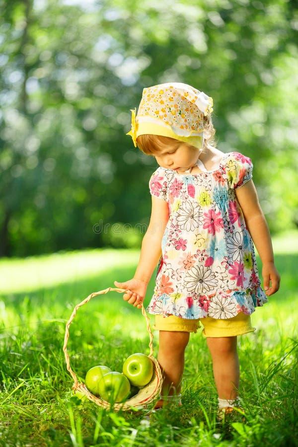 Meisje op gras met mand van appelen royalty-vrije stock afbeeldingen