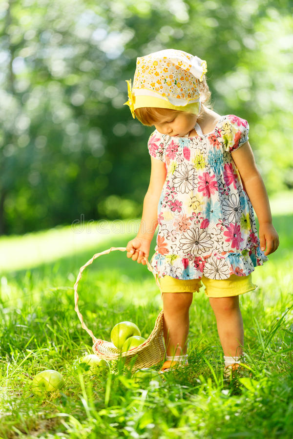 Meisje op gras met mand van appelen royalty-vrije stock fotografie