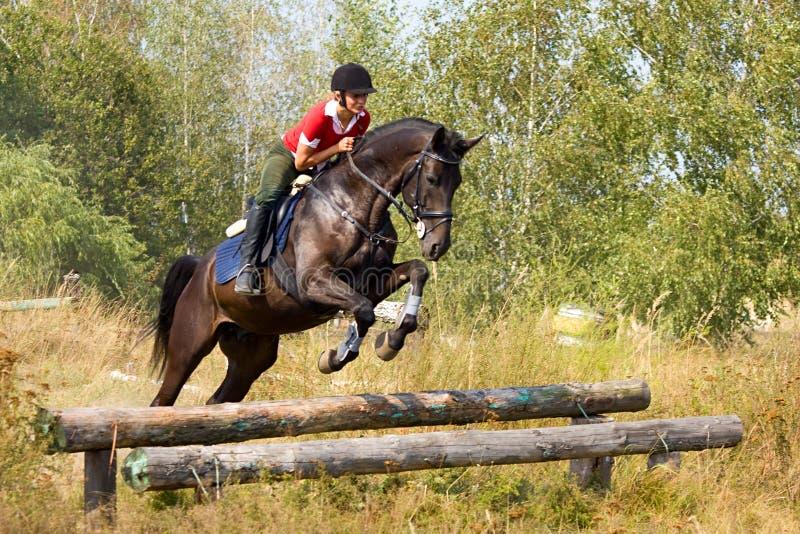 Meisje op het springen paard stock foto's