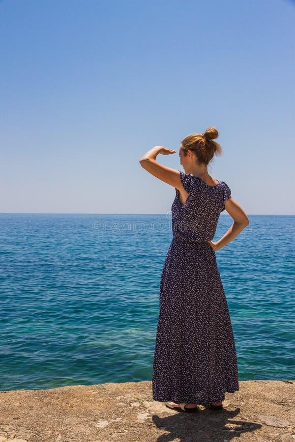 Meisje op het strand die de afstand onderzoeken stock afbeelding