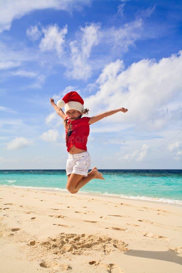 Meisje op het strand in het rood van de Kerstman stock afbeelding