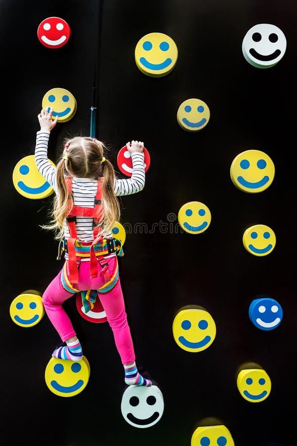 Meisje op jonge geitjes bergbeklimmingsmuur royalty-vrije stock afbeelding