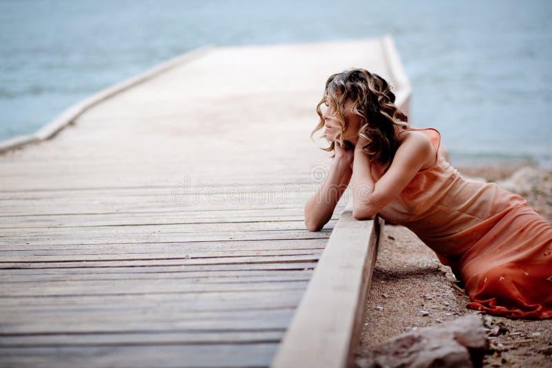 Meisje op ligplaats dichtbij overzees royalty-vrije stock foto