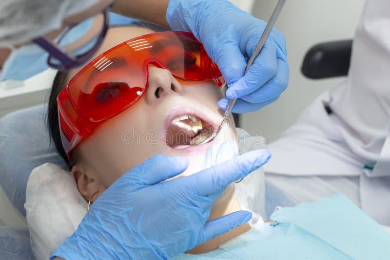 Meisje op onderzoek bij tandartsbehandeling van carieuze tand de arts gebruikt een spiegel op het handvat en een boriummachine stock afbeeldingen
