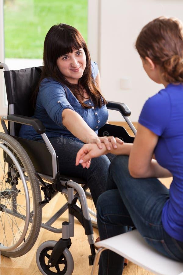 Meisje op rolstoel die met vrouwelijke vriend spreken stock afbeelding