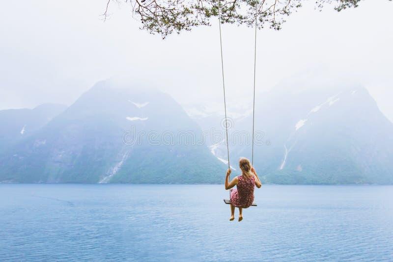 Meisje op schommeling in Noorwegen, gelukkige escapist, inspiratieachtergrond royalty-vrije stock afbeelding