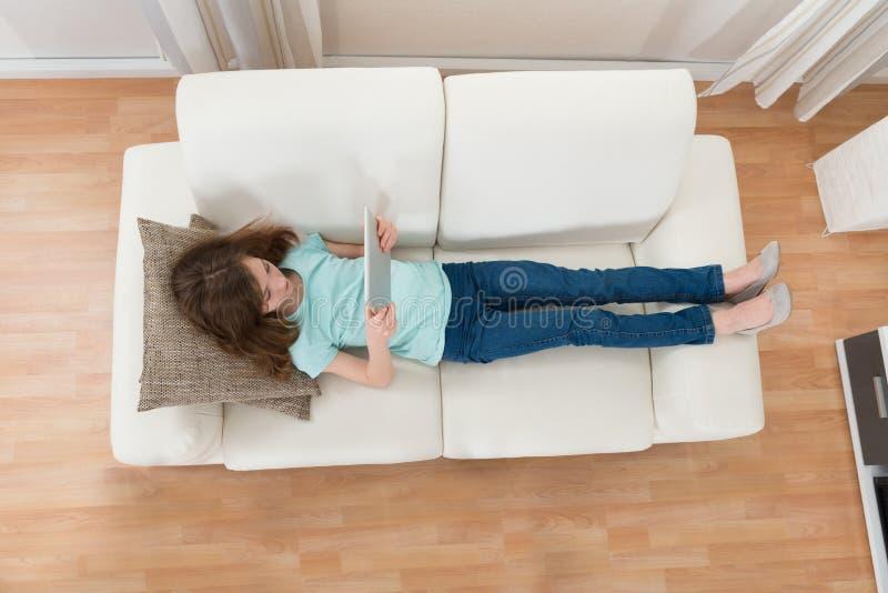 Meisje op Sofa Using Digital Tablet royalty-vrije stock foto's