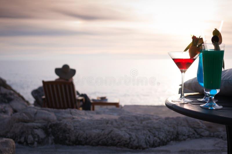 Meisje op strand die zonsondergangcocktail hebben royalty-vrije stock afbeelding