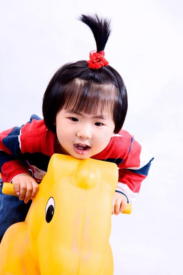 Meisje op stuk speelgoed paard royalty-vrije stock afbeeldingen