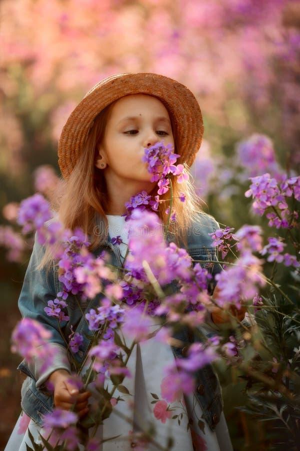 Meisje openluchtportret in roze bloemen royalty-vrije stock afbeelding