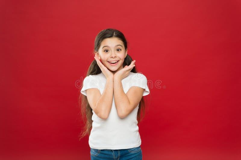Meisje opgewekt het glimlachen gezicht Voelt het jong geitje gelukkige leuke gezicht opgewekte rode achtergrond Opwindende ogenbl stock fotografie
