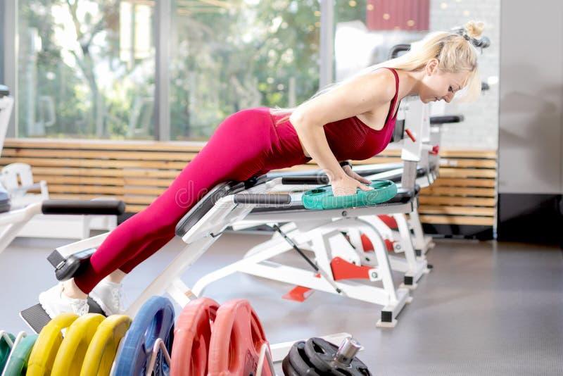 Meisje in opleiding in de gymnastiek Vrouwelijke geschiktheid stock afbeelding