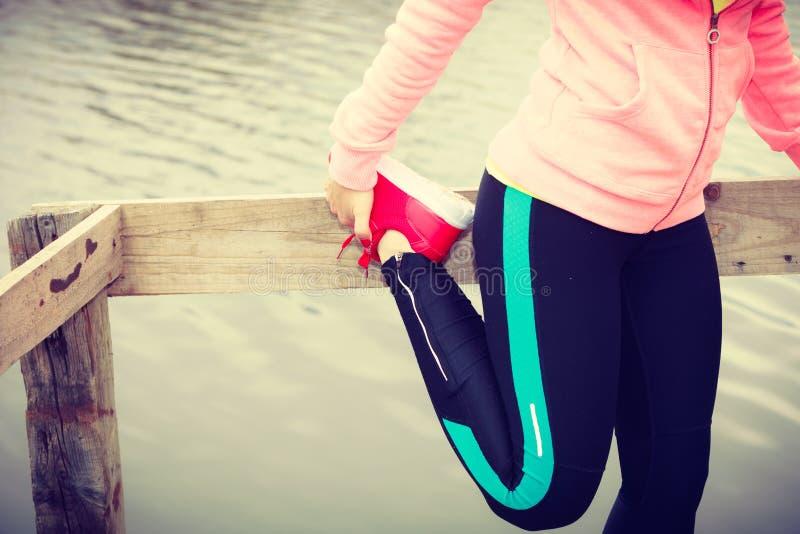 Meisje opleiding in sportieve kleren op meerkust stock foto