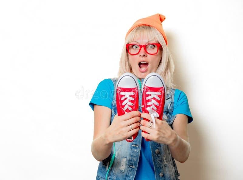 In meisje in oranje hoed met rode gumshoes royalty-vrije stock fotografie