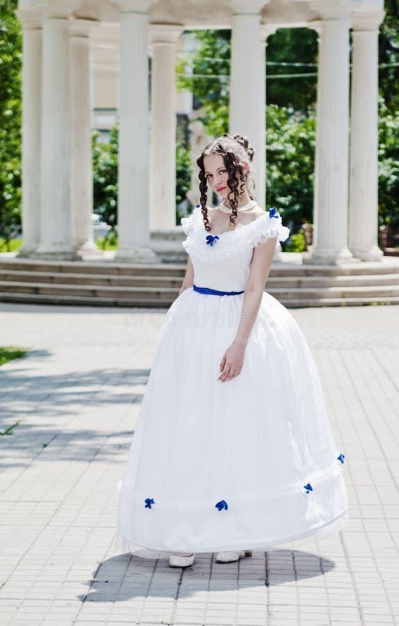 Meisje in oude kleding met hoepelrok op de achtergrond van de rotonde stock afbeeldingen