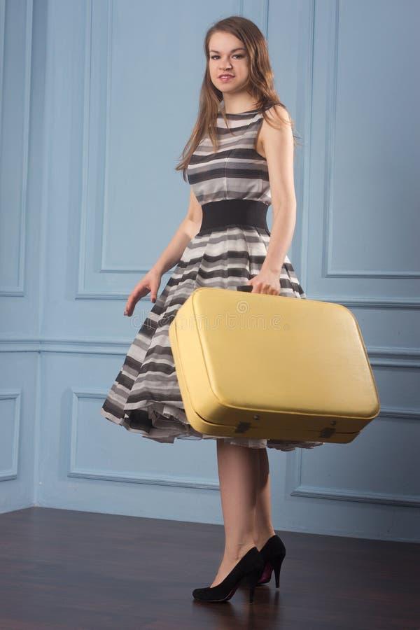 Meisje in ouderwetse stipkleding met oude koffer stock afbeelding