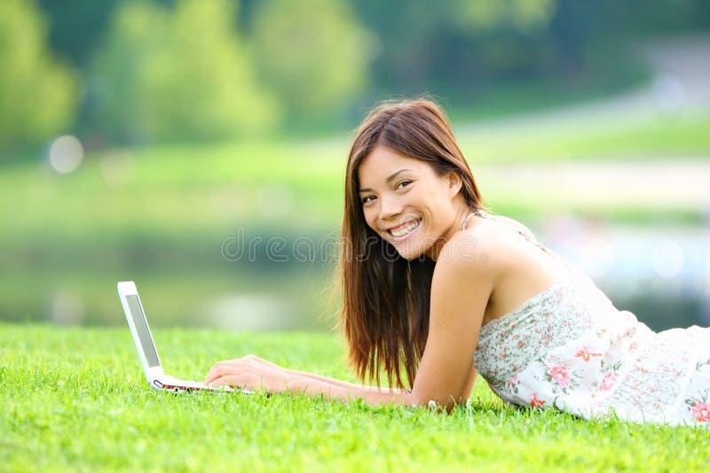 Meisje in park op laptop stock afbeelding