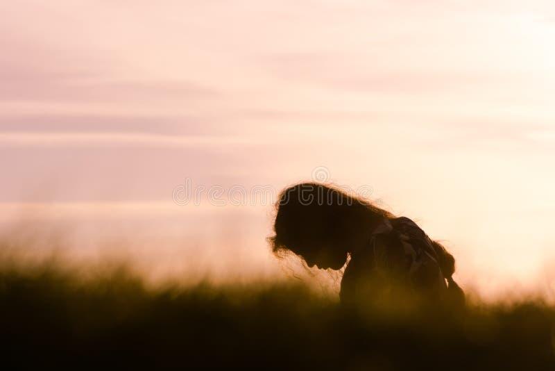 Meisje in profiel voor purpere zonsondergang wordt gesilhouetteerd die royalty-vrije stock fotografie