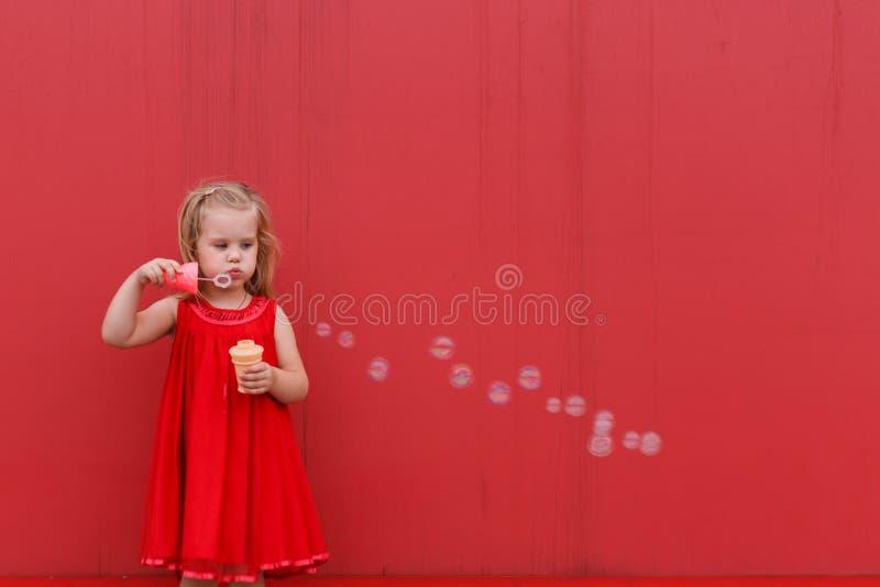 Meisje in rode drtess die zeepbels op de achtergrond blazen stock foto