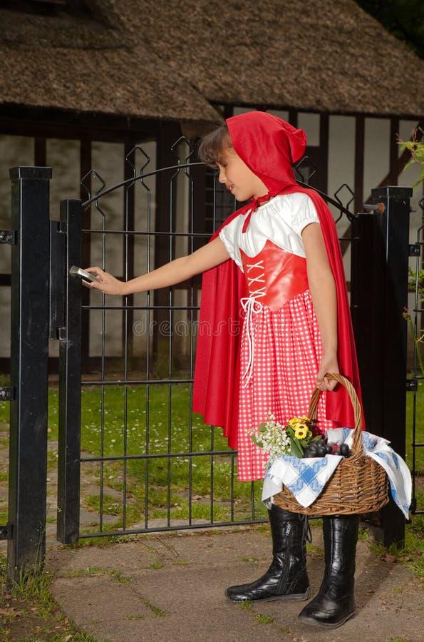 Meisje in rode het openen poort royalty-vrije stock afbeelding