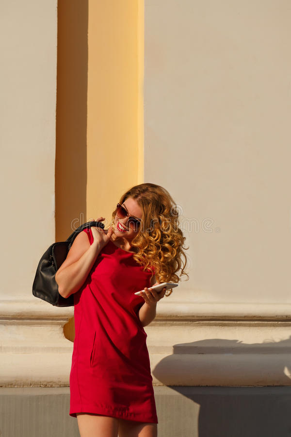 Meisje in rode kleding en met in handtas, telefoon royalty-vrije stock foto