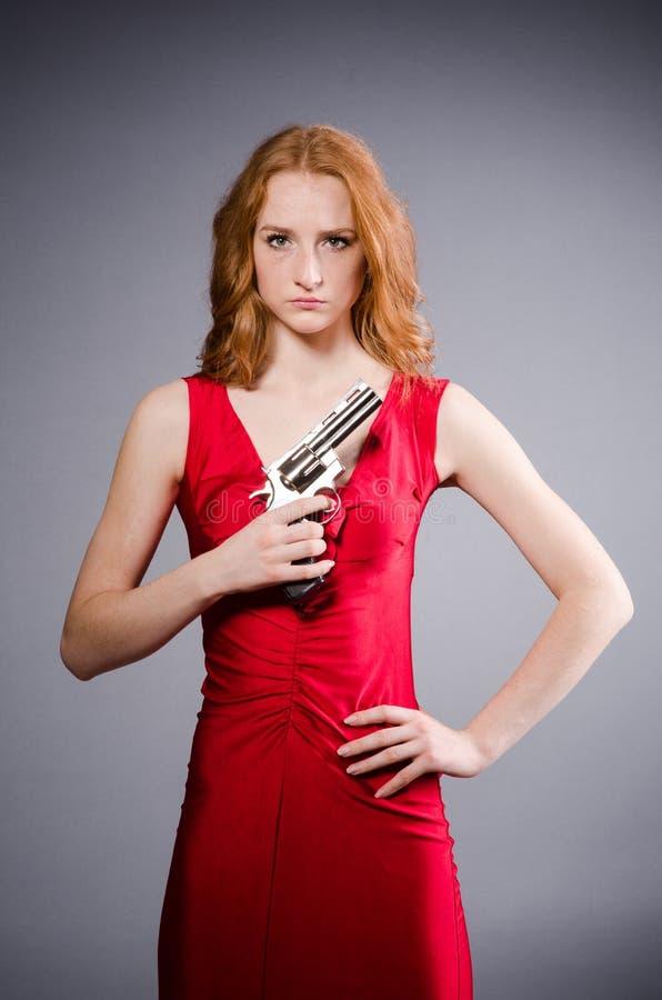 Meisje in rode kleding met pistool tegen grijs stock afbeelding
