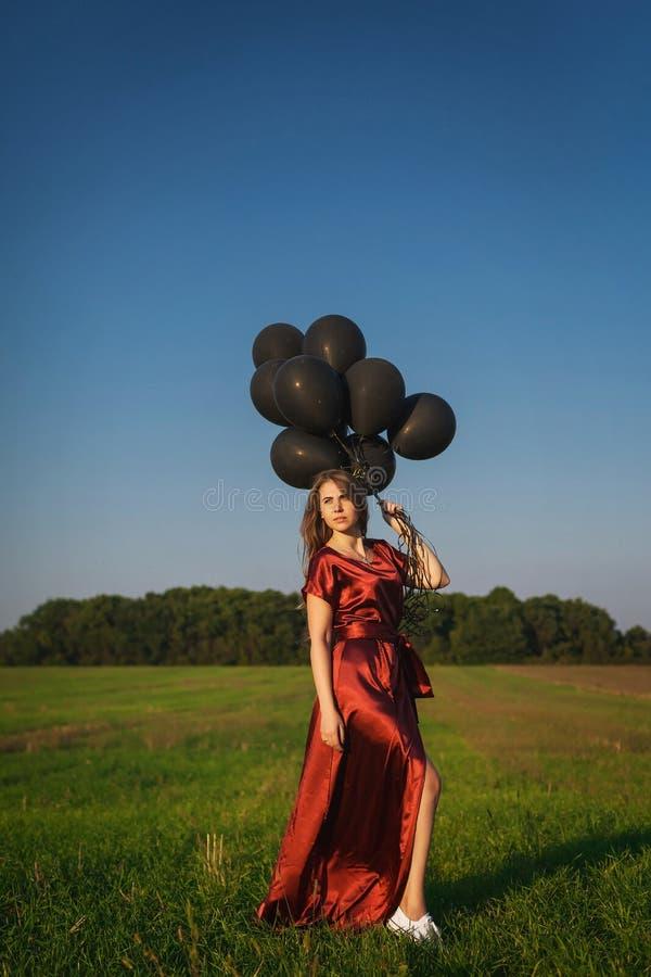 Meisje in rode kleding met zwarte ballons die zich op een gebied bevinden stock foto