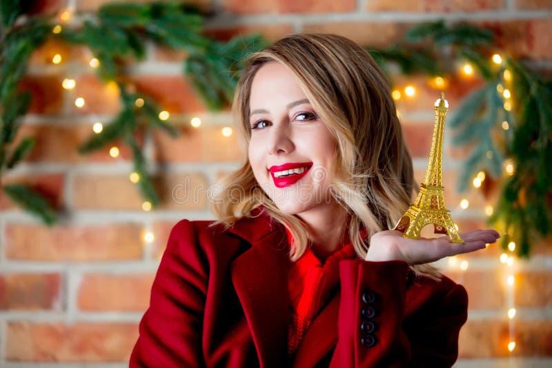 Meisje in rode laag met gouden de torenherinnering van Eiffel stock foto's