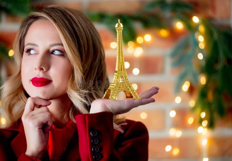 Meisje in rode laag met gouden de torenherinnering van Eiffel stock foto