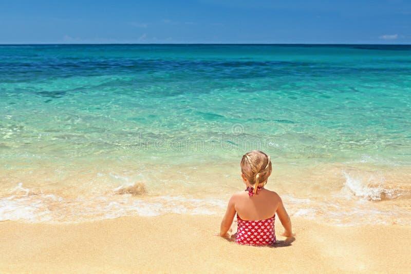 Meisje in rode zwempakzitting op de rand van het zandstrand stock foto's