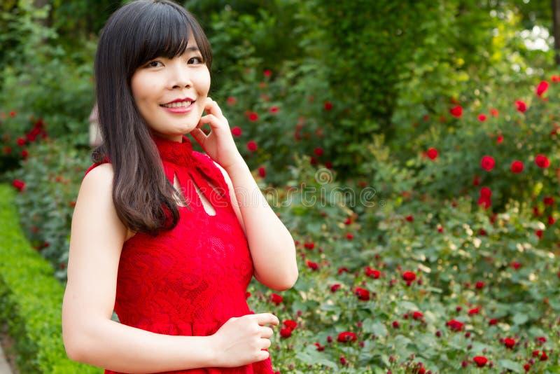 Meisje in rood bij roze tuin stock fotografie