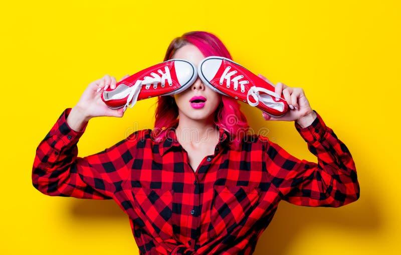 Meisje in rood geruit Schots wollen stofoverhemd en gumshoes stock fotografie