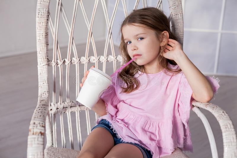 Meisje in roze kleding het drinken milkshake als Voorzitter royalty-vrije stock foto