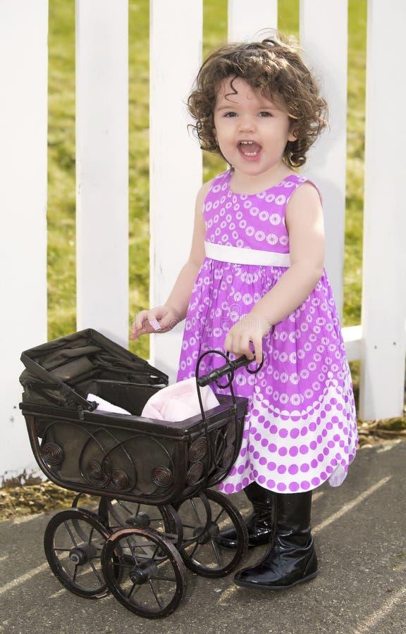 Meisje in roze kleding met een kinderwagen stock afbeeldingen