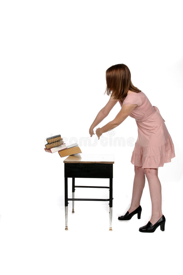Meisje in roze kledings dumpende boeken van het bureau stock afbeelding