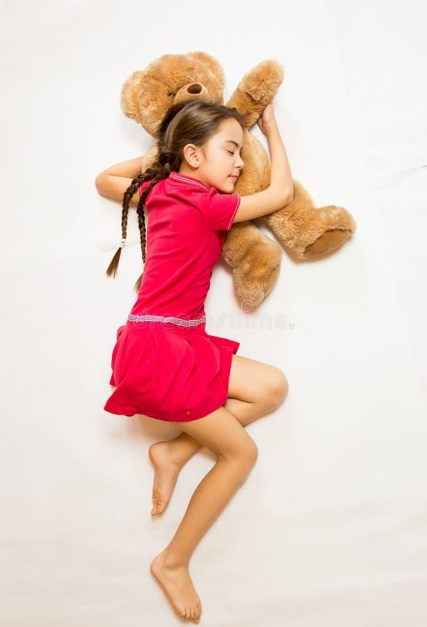 Meisje in roze kledingsslaap op grote teddybeer op vloer stock foto