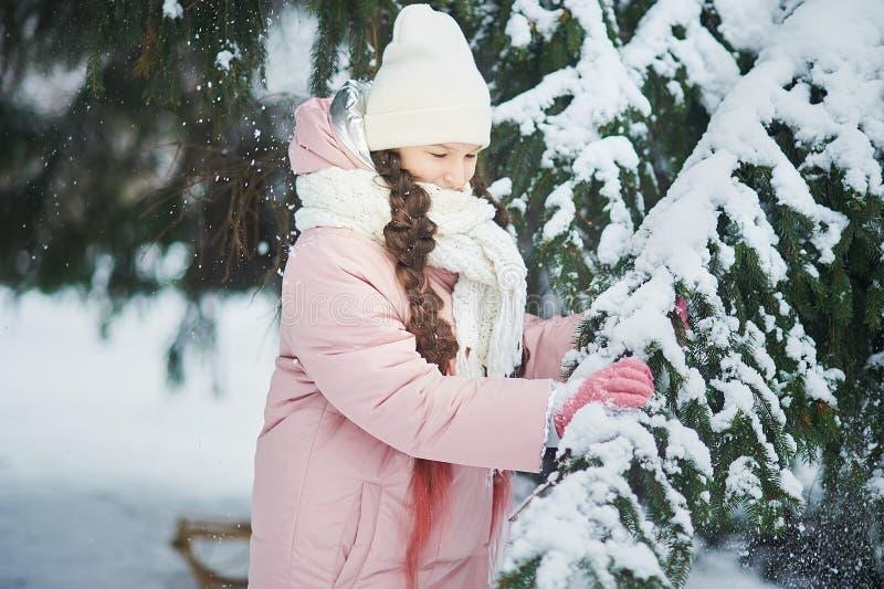 Meisje in roze laag in sneeuwpark Meisjesspelen in de winterpark Aanbiddelijk kind die in bos de aanrakings houten tak van de sne royalty-vrije stock afbeeldingen