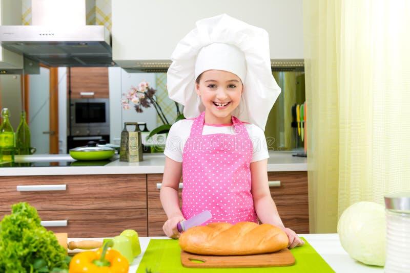 Meisje in roze schort scherp brood royalty-vrije stock foto's