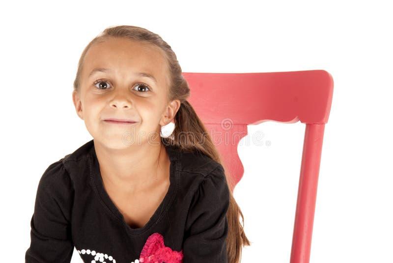 Meisje in roze stoel dichte omhooggaand met een kaasachtige grijns stock foto