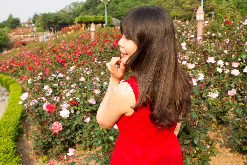 Meisje in roze tuin wordt geglimlacht die royalty-vrije stock fotografie