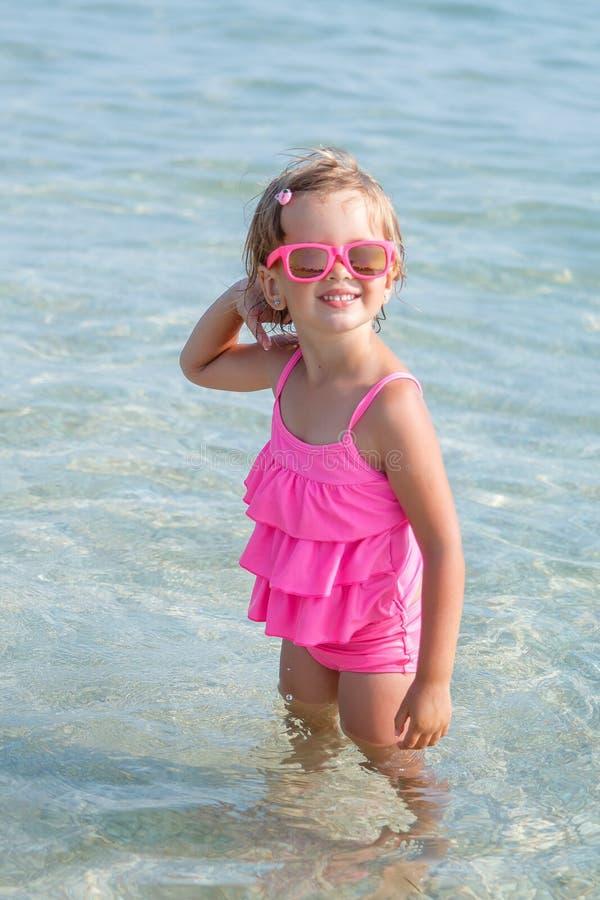 Meisje in roze zwempak en zonnebril bij de overzeese stellende camera Gelukkig, het glimlachen De vakantie van de zomer stock foto's