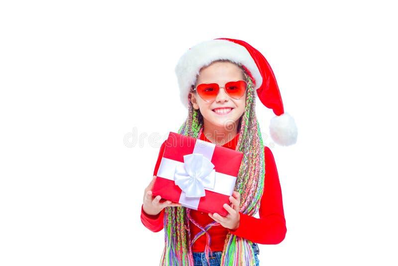Meisje in santa` s hoed Het portret van weinig leuke doos van de meisjesholding van Kerstmis huidig, Klein meisje koestert haar g royalty-vrije stock foto's