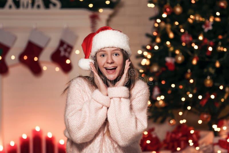 Meisje in santahoed dichtbij Kerstmisboom royalty-vrije stock afbeeldingen