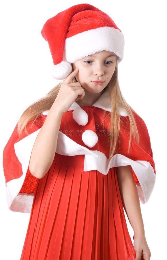 Meisje in santahoed die aan de gift wordt gedacht stock foto