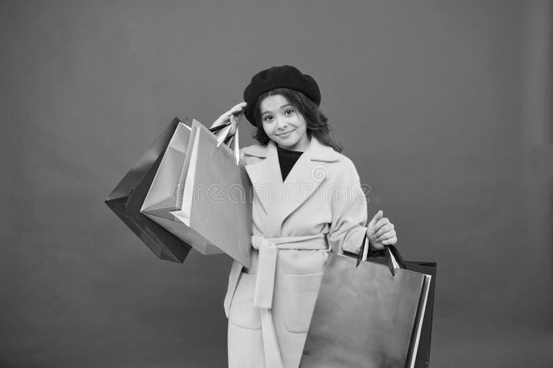 Meisje schattige jongen houdt boodschappentassen rode achtergrond vast Winkelen met korting op feestdagen Fashionista adore shopp stock afbeelding
