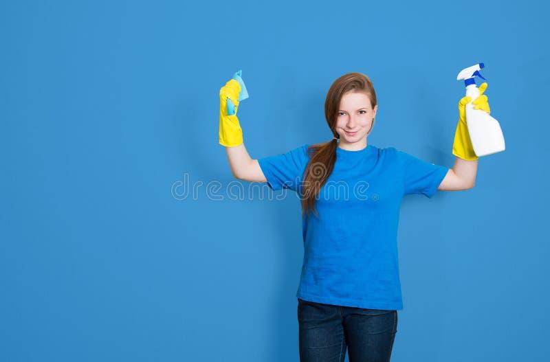 Meisje schoonmaakster met het schoonmaken van nevelfles de schoonmakende dienst stock foto