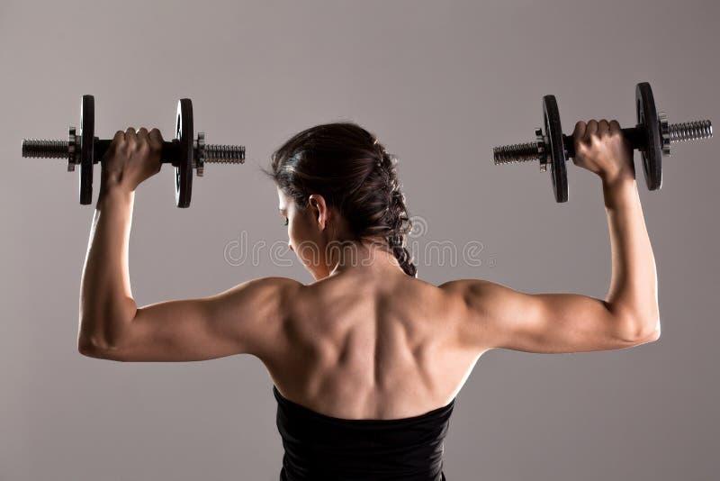 Meisje in sexy zwarte kleding het opheffen gewichten stock foto